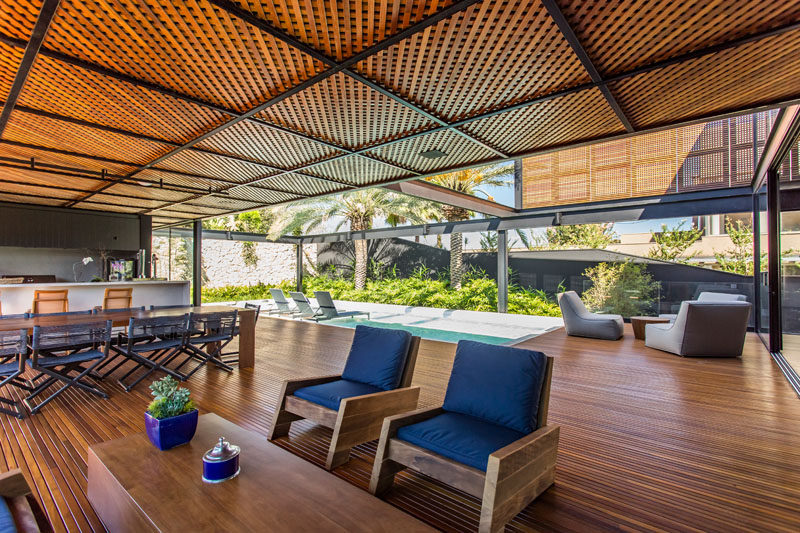 This modern house has a covered entertaining area with an outdoor kitchen, dining area, and lounge. #ModernHouse #WoodCeiling #EntertainingArea #OutdoorSpace