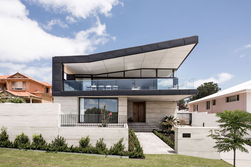 The roof, along with an angular plan, allows this modern house to take advantage of the views of the surrounding area, while black zinc has been used on the upper half of the house to create contrast with the light colored exterior walls. #ModernHouse #ModernArchitecture #HouseDesign #CurbAppeal