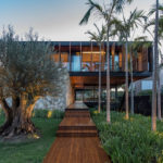 This Modern Tropical Home Floats Above A Base Of Stone And Glass