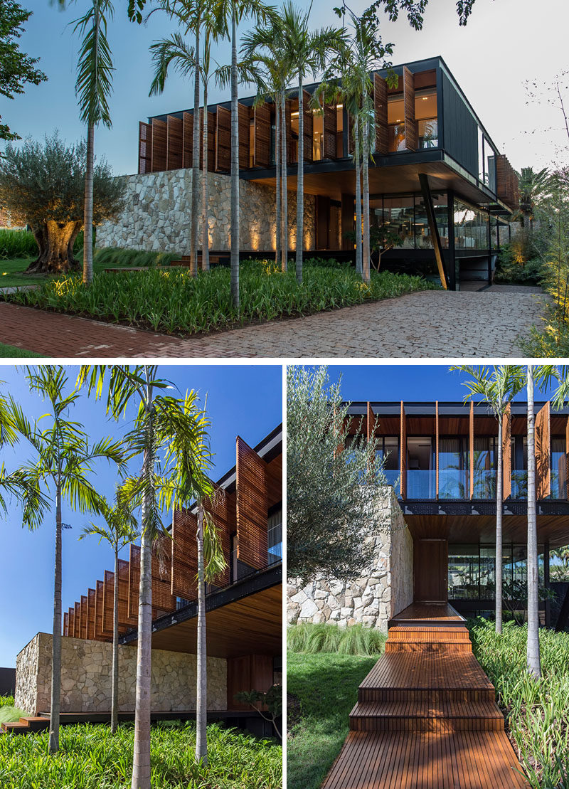 At the front of the multi-storey house, a wood path leading to the front door is surrounded by lush landscaping on one side, and a lawn with a single tree on the other. #ModernHouse #HouseDesign #ModernArchitecture #Landscaping