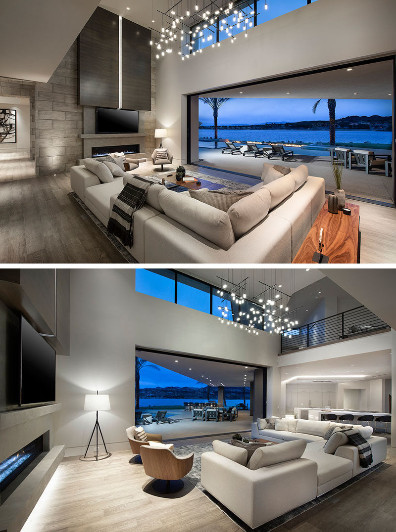 Large sliding glass doors connect this modern great room, which features an artistic light installation, to the outdoors. #ModernGreatRoom #ModernLivingRoom #Fireplace #Lighting