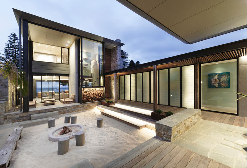 This modern house has a interior courtyard with sand and a fire pit. #FirePit #Courtyard #BeachHouse