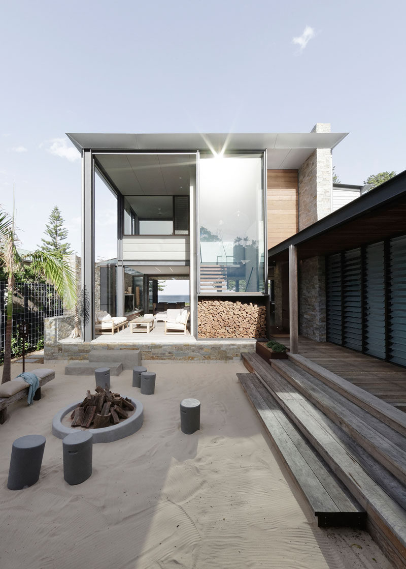 This modern house opens to a sandy courtyard with a fire pit and stool/bench seating. #Courtyard #Firepit #Landscaping #Architecture