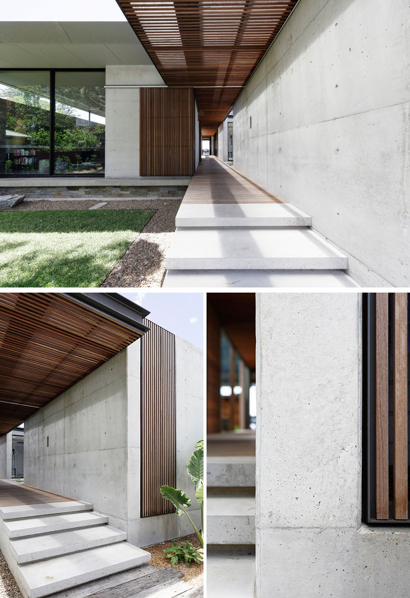 Concrete stairs alongside a concrete wall, lead to the sliding wood slat front door, that complements the breezeway that runs throughout this modern house. #WoodSlats #FrontDoor