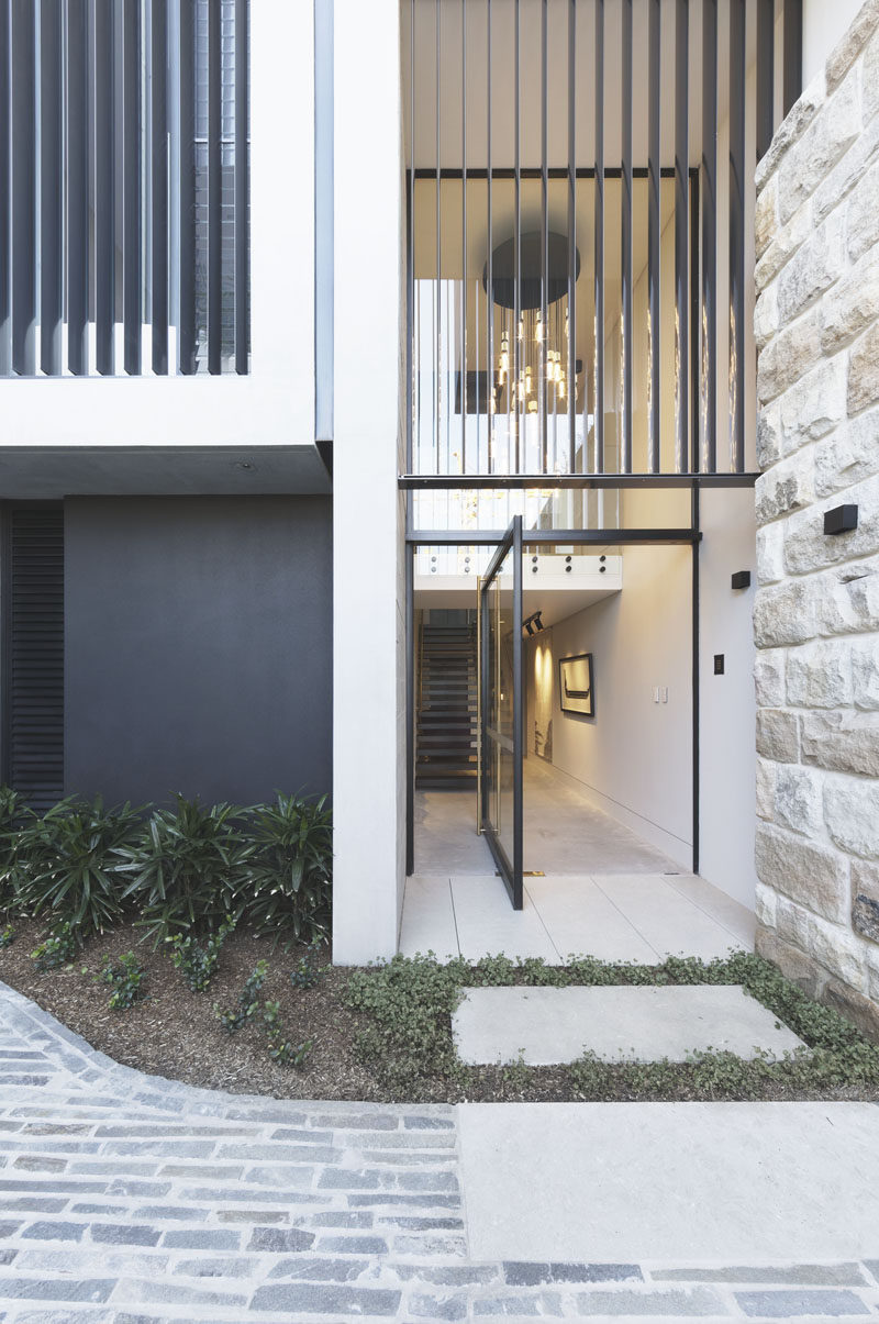 A large pivoting glass front door welcomes visitors to this modern house. #FrontDoor #PivotingDoor #GlassFrontDoor