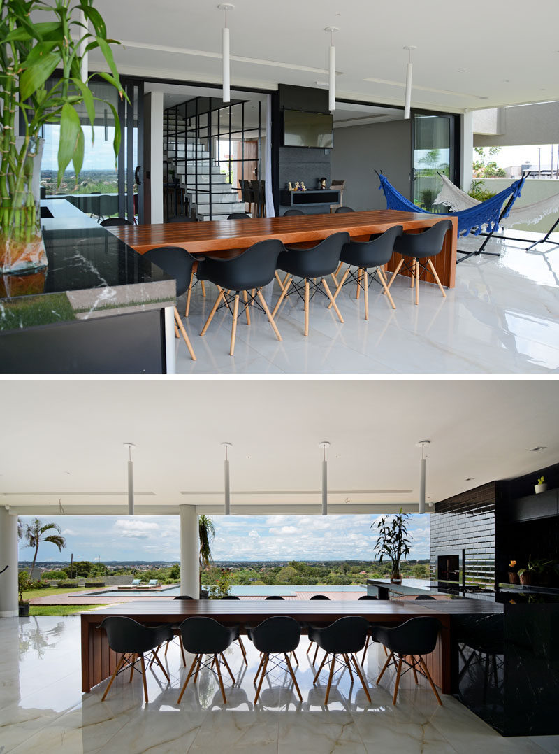 The ground floor of this modern house is dedicated to the living areas, with a covered outdoor entertaining space featuring a large wood dining table, and a black kitchen. #DiningTable #BlackKitchen