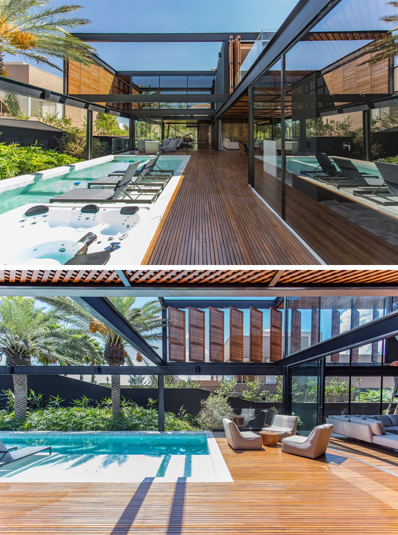 This modern house has an outdoor area that lies adjacent to the swimming pool, while large sliding glass walls open to create an indoor / outdoor living experience. #ModernSwimmingPool #ModernHouse