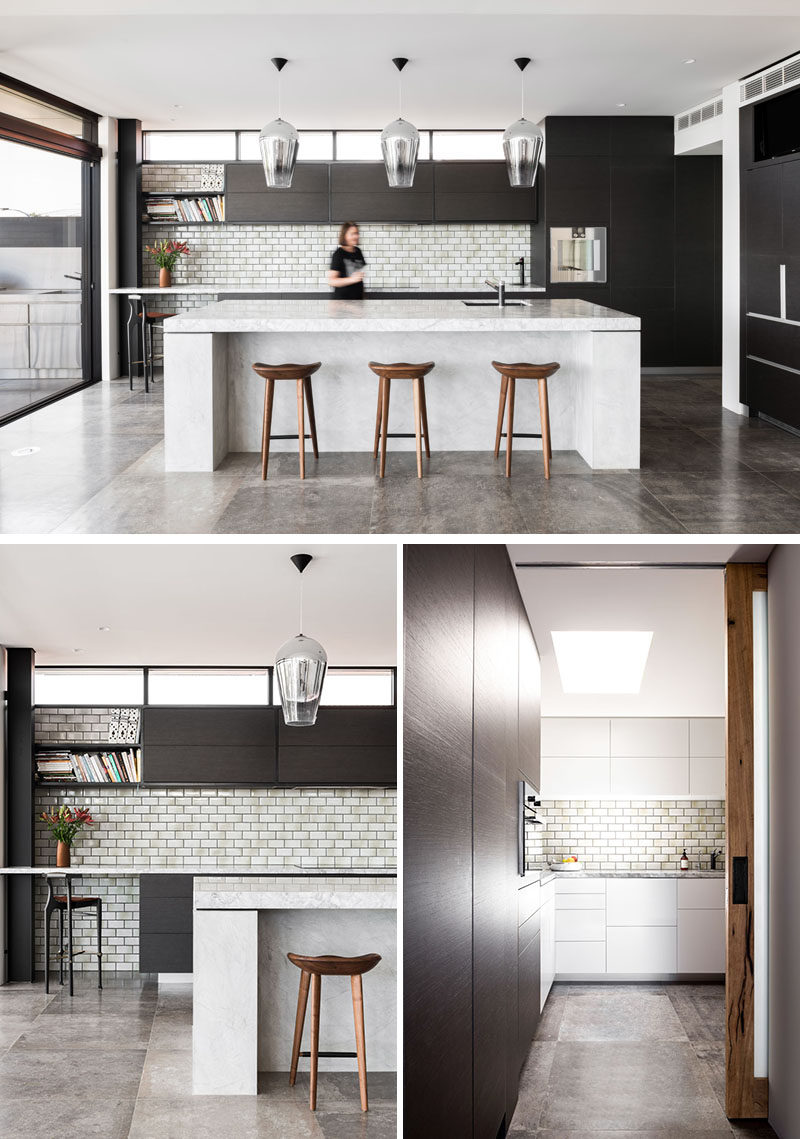In this modern kitchen, subway tiles complement the light colored countertop and large island, while a pantry is tucked away off to the side through a pocket door. #ModernKitchen #DarkWoodCabinets #KitchenIsland #Pantry