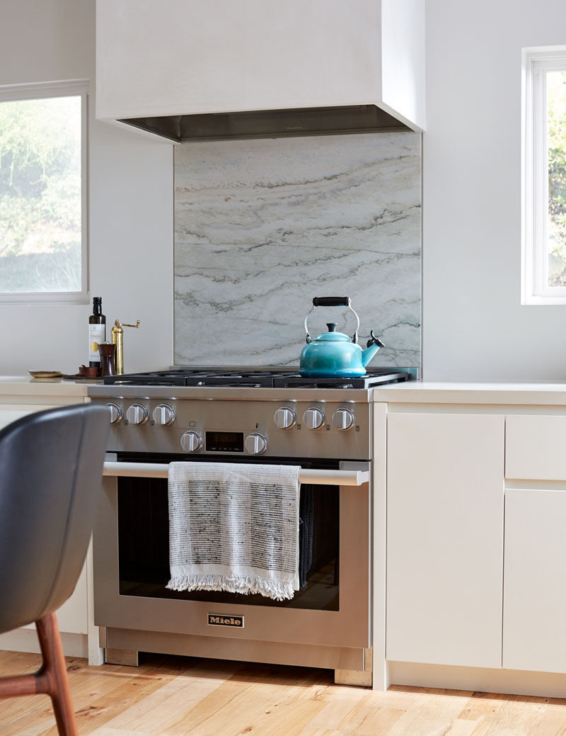 This modern kitchen has recessed finger pulls instead of traditional hardware on the cabinets have been included to keep the look modern without being too cold. #ModernKitchen #KitchenDesign #KitchenCabinets