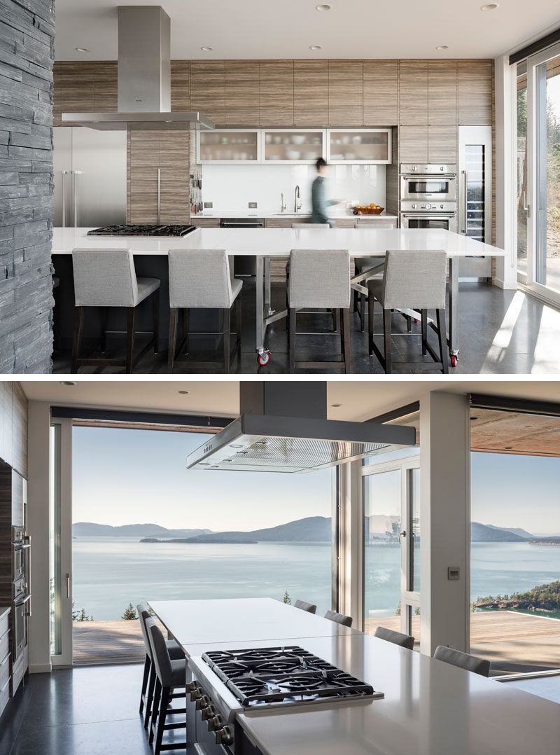 In this modern kitchen, minimalist hardware-free wood cabinets line the wall, and a large white kitchen island provides plenty of counterspace. A movable dining table has been designed to extend the kitchen island, or be wheeled outside onto the deck to be used for alfresco dining. #ModernKitchen #WoodCabinets #KitchenIsland #MoveableKitchenIsland