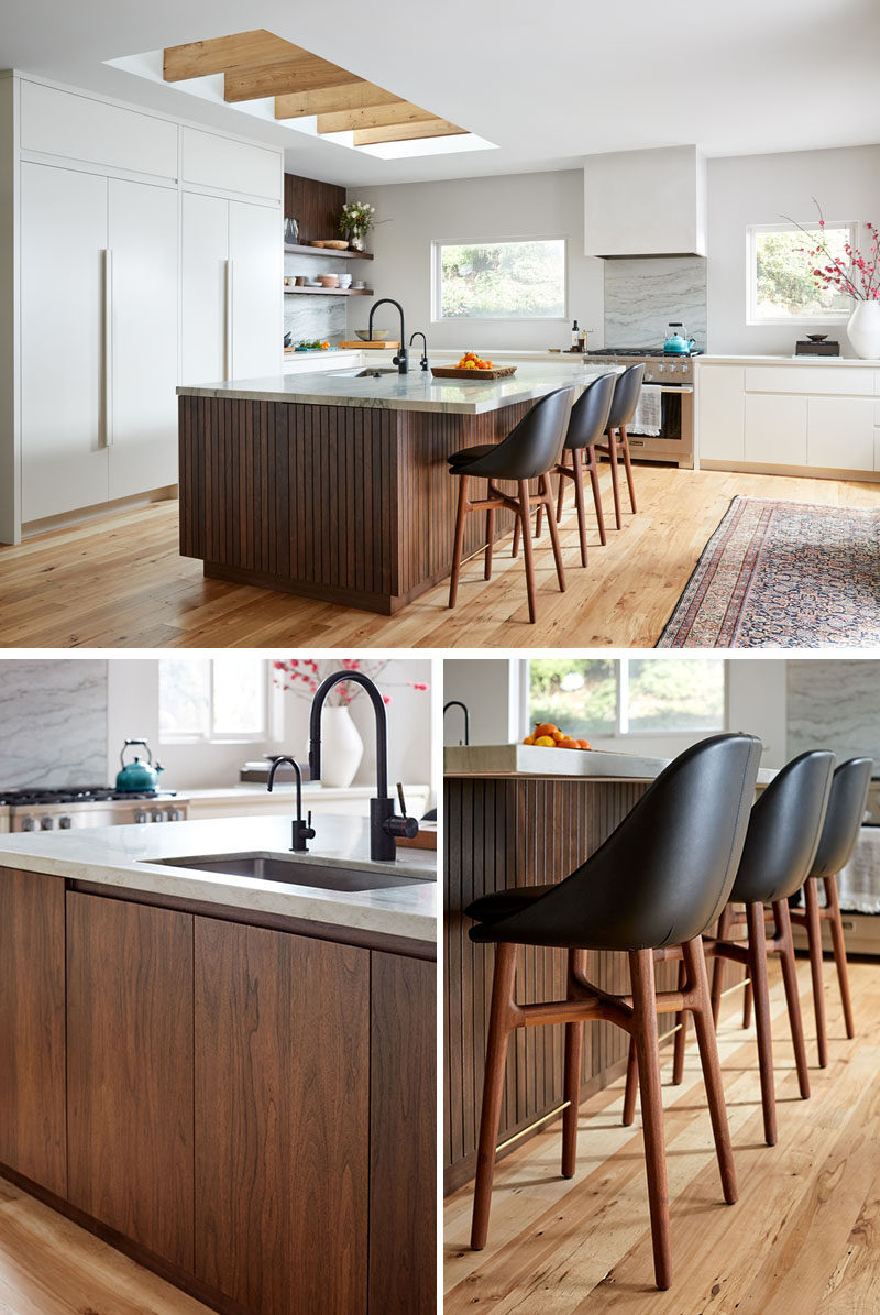 This modern kitchen utilizes sleek, bright cabinetry, and various wood tones to keep the space grounded and warm. #ModernKitchen #KitchenDesign #WoodKitchenIsland