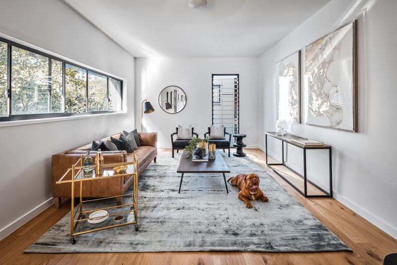 In this modern living room, a row of windows provides natural light, while louver windows allow the flow of air through the room.