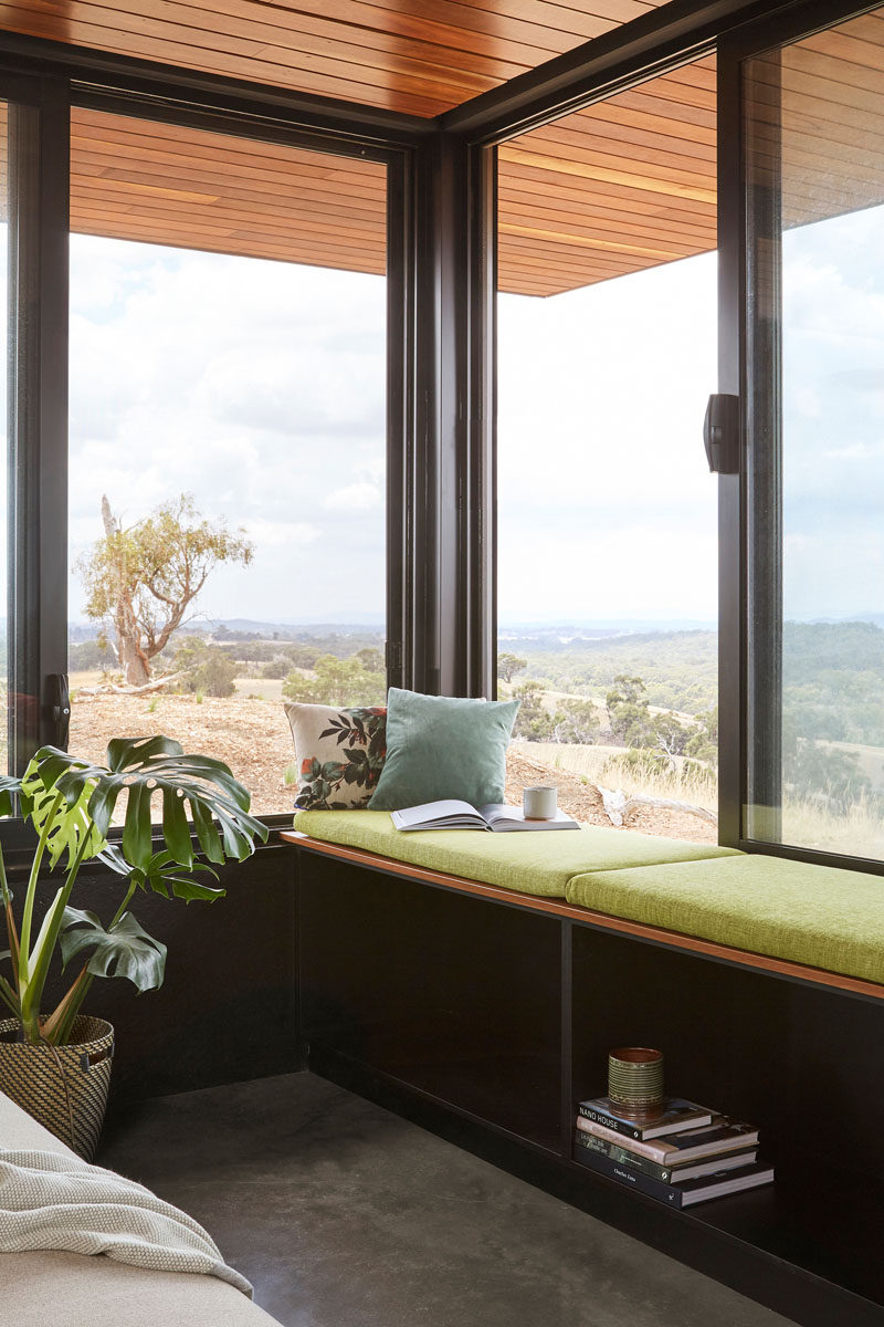 A wall of windows adds natural light to the open-plan social areas of this modern house, and a built-in window seat allows a restful place to enjoy the views. #WindowSeat #Windows