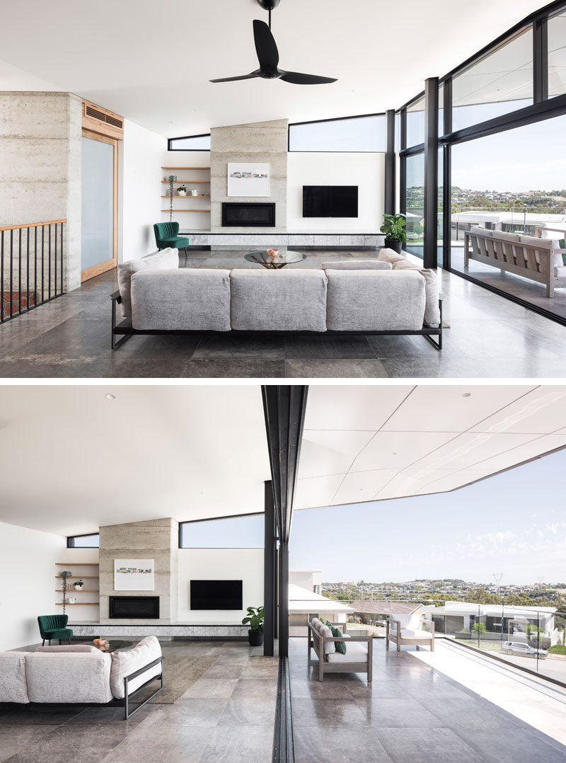 This modern living room, which features a fireplace,seamlessly transitions to the outdoor balcony via a huge expanse of glass and oversize sliding doors. #LivingRoom #Fireplace #Balcony