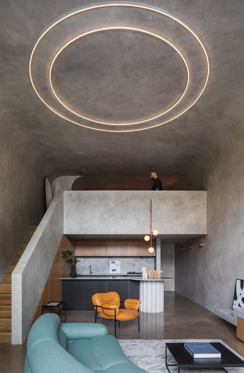 This minimalist open plan apartment features a custom kitchen and a mezzanine bedroom which overlooks the living room space and small terrace. #LoftApartment #ApartmentDesign #Kitchen
