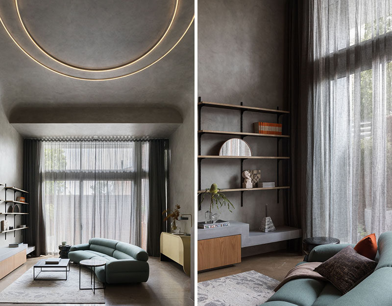 This minimalist loft is flooded with light from a full height, glazed wall, counterbalancing the interior mood, which is intentionally dark and brooding. #Loft #LoftApartment #LivingRoom #Windows