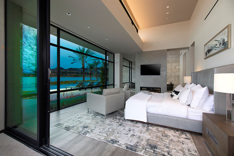 In this modern master bedroom suite, there's a sitting area that's separated from the sleeping area by a partial wall with a television and fireplace. #ModernBedroom #MasterBedroom