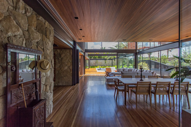 The social areas of this modern house are located on the main floor of the home. Large aluminum and glass frames help to bring the landscaping into the interior environments, making them appear larger. #ModernHouse #StoneWall #InteriorDesign