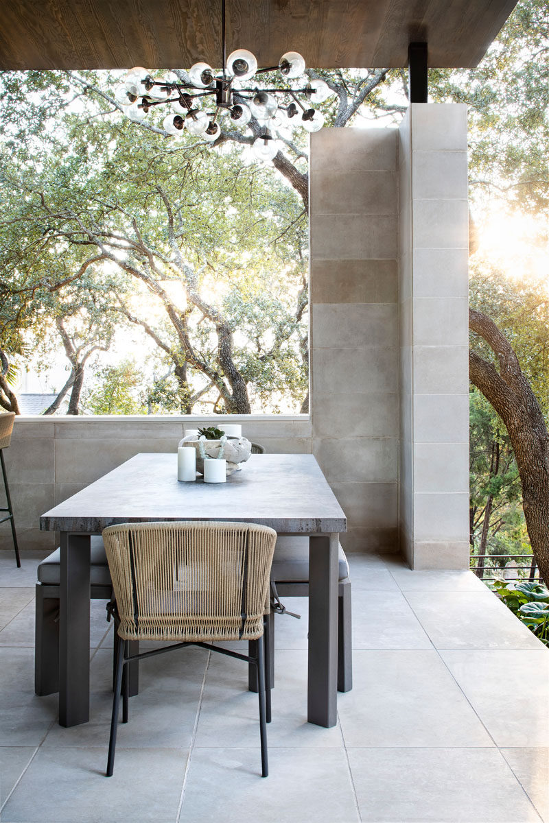 A chandelier hangs high above the alfresco dining area, while an opening in the wall provides views of the trees. #OutdoorPavilion #OutdoorDining #AlfrescoDining