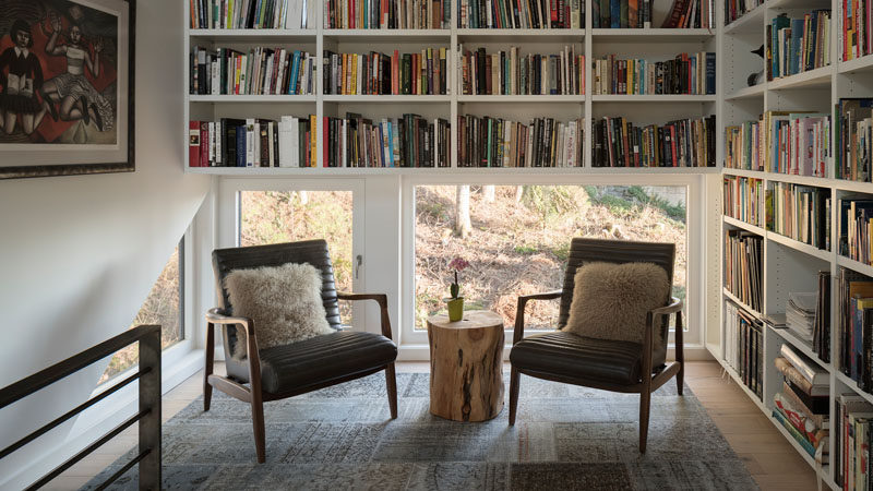 This modern house has a small library with low windows and floor-to-ceiling shelving. #SmallLibrary #Library #ReadingNook #Shelving #Windows
