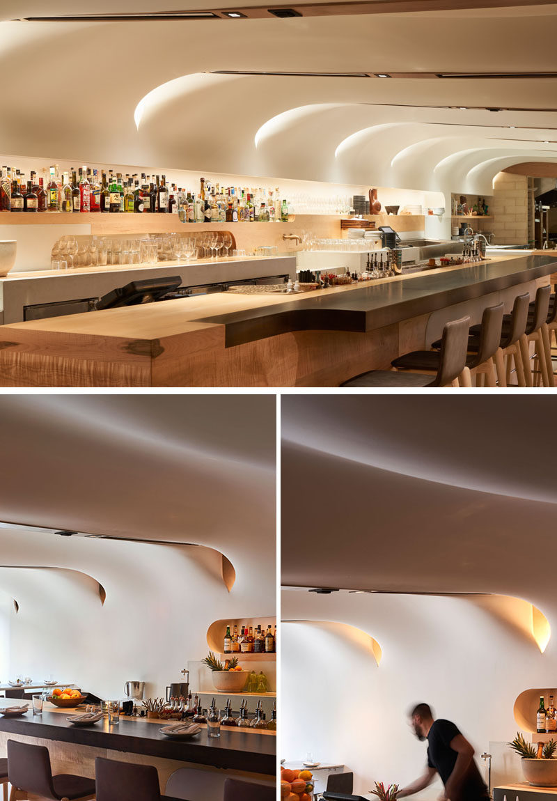 The white, undulating ceiling of this modern restaurant is composed of glass fibre-reinforced gypsum, whilethe bar anddetails feature Canadian maple and Ductal concrete. #ModernRestaurant #RestaurantDesign #InteriorDesign