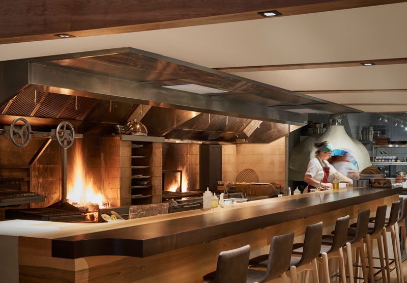 This modern restaurant's open galley kitchen is a 24-foot-long, open-flame grill that runs the length of the space, #ModernRestaurant #RestaurantDesign #RestaurantKitchen