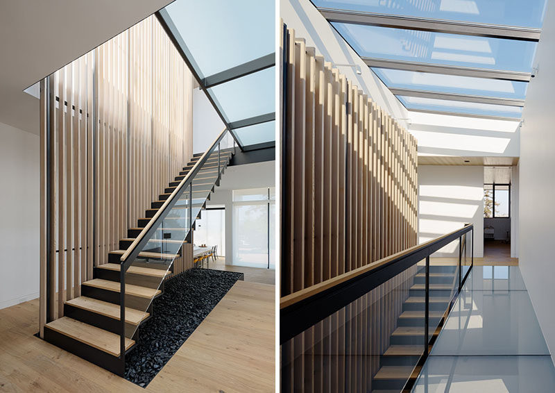 This modern bent-steel staircase runs alongside a wood slat feature and leads up to the bedrooms. A series of windows floods the stairs with natural light. #Stairs #WoodStairs #SteelStairs