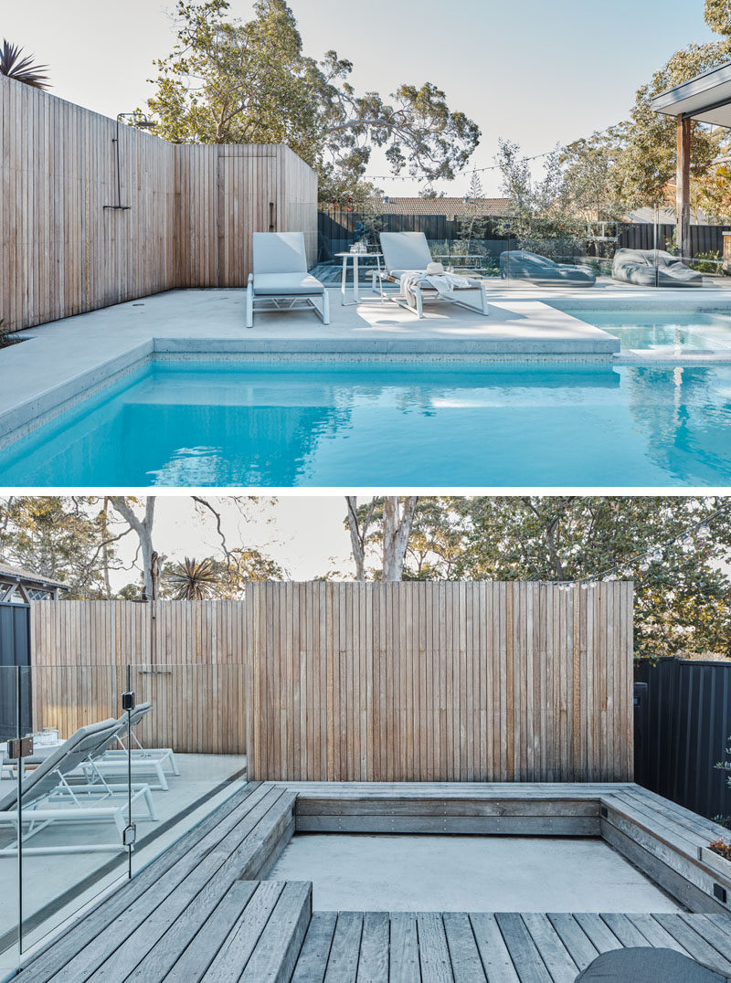 A deck with wood fencing surrounds this modern pool, while a glass safety fence almost appears invisible. A sunken seating area provides additional room for entertaining. #SwimmingPool #ModernPool #ModernDeck