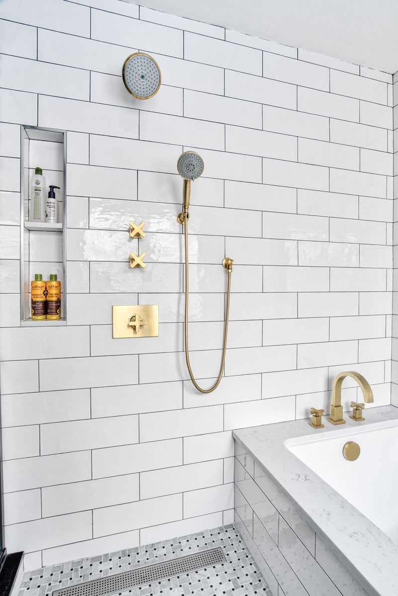 In this modern bathroom, a small nook for storing bathroom items was built-in next to the shower heads to keep them tucked away and out of sight from the rest of the bathroom. #Shower #BuiltInShelving #ModernBathroom #BathroomDesign