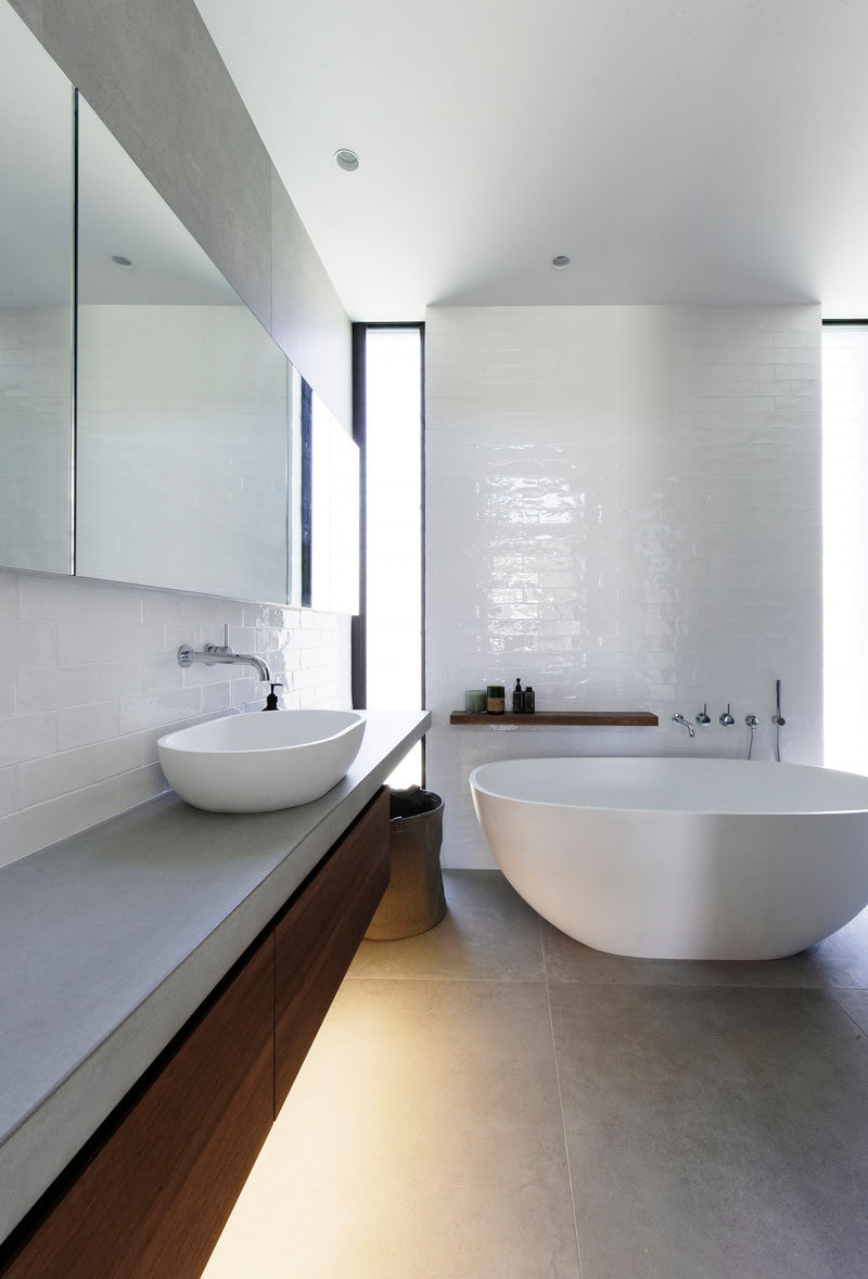 In this modern bathroom, a white freestanding bathtub has been placed beside a glossy tile wall, while a wood vanity and shelving adds a natural touch to the room. #ModernBathroom #BathroomDesign #Bathroom