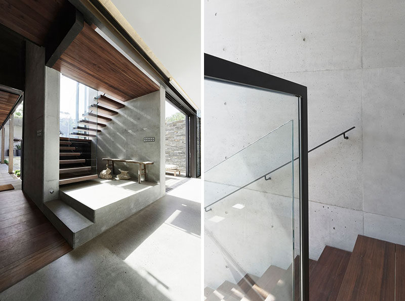 Wood and concrete stairs with a glass railing lead to the upper floor of this modern house. #Stairs #WoodStairs