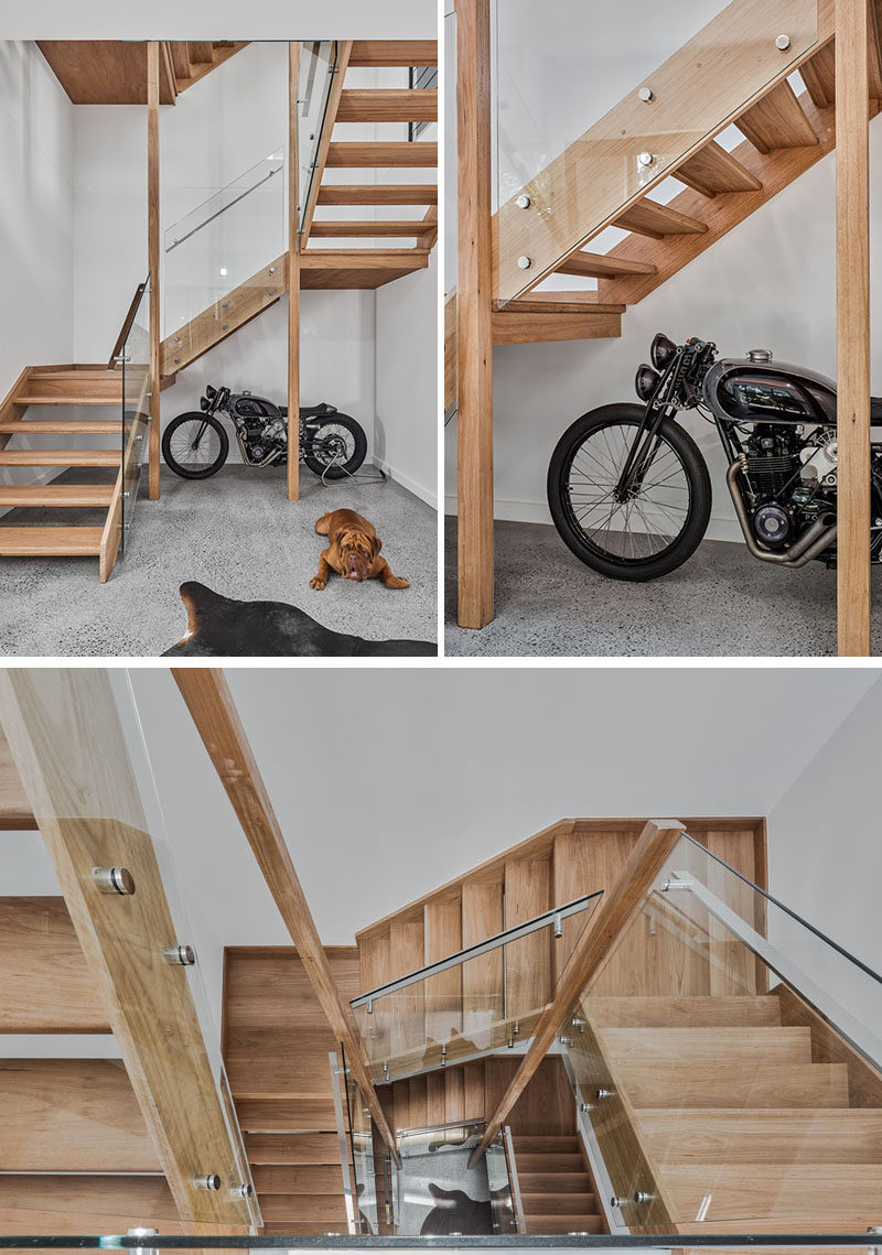 Inside this modern house, there's a wood staircase with glass handrails that lead from the garage up to the social areas of the house and bedrooms on the top floor. #ModernWoodStairs #WoodStairs