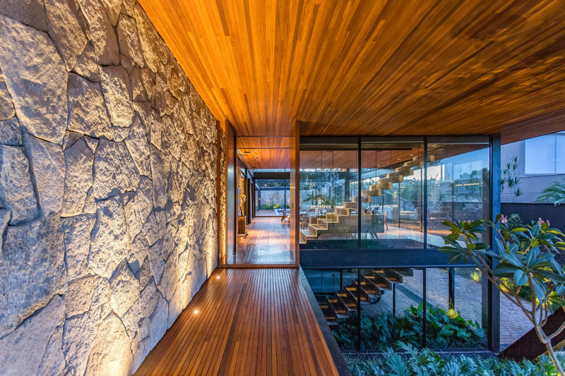 Wood veneers, natural stones, and metal sheets were incorporated into the design of this modern house, helping to define the volumes and making the interior spaces more welcoming. #ModernHouse #StoneWall #WoodCeiling #ModernArchitecture