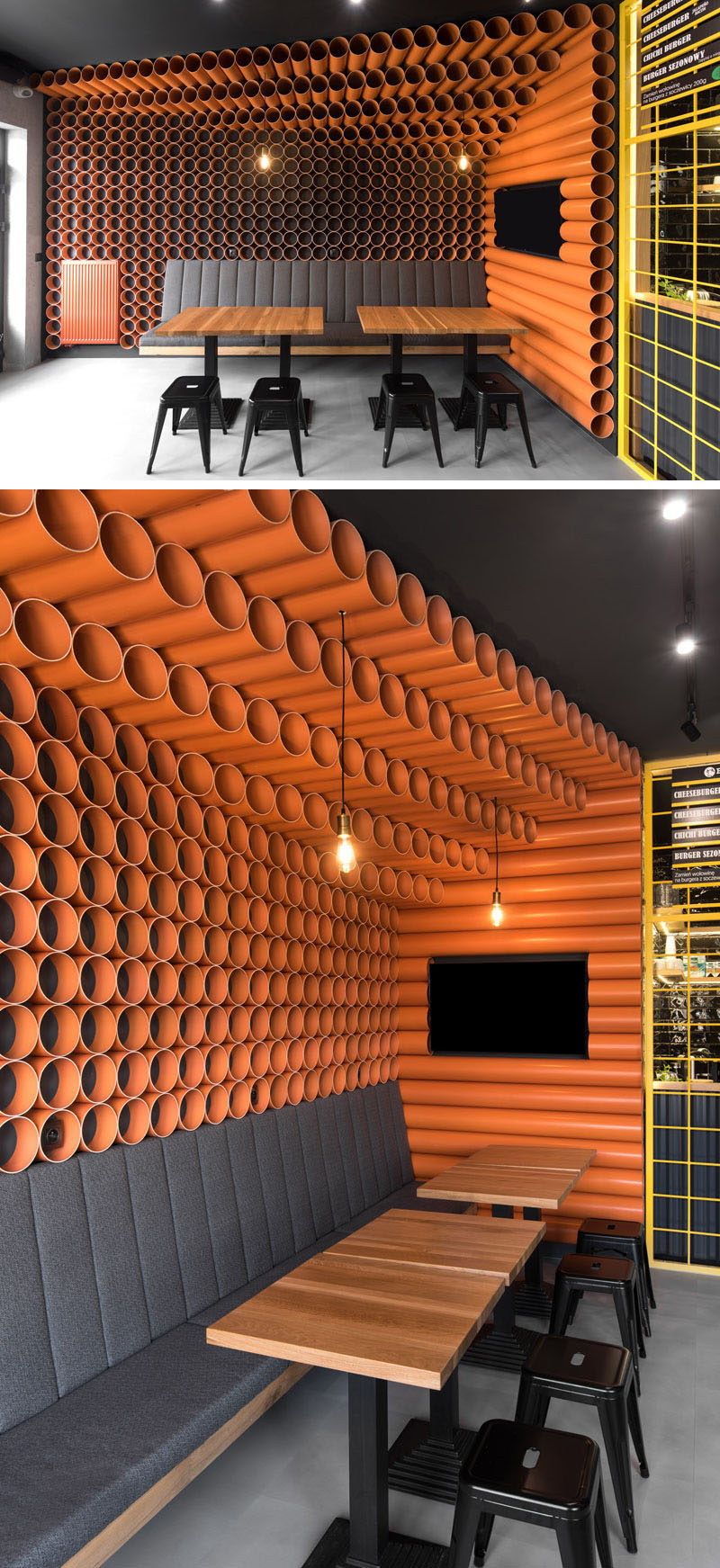 This modern restaurant features almost 300 bright orange PVC pipes that cover the walls and ceilings, while upholstered seating and tables run along the walls, create a comfortable place to sit and eat. #RestaurantDesign #ModernRestaurant #PVCpipes
