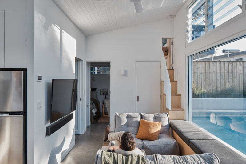 This small house includes a kitchen, living room with a built-in window seat overlooking the pool, 2 bedrooms (sleeping 4), a play space, and a bathroom. #SmallHouse #TinyLiving #MicroLiving