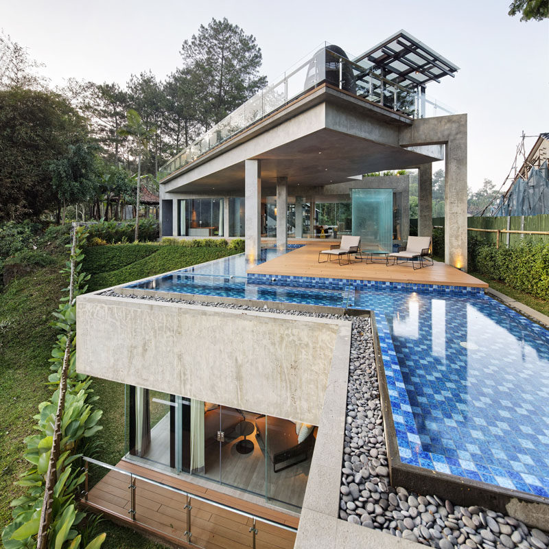 This modern house in Indonesia has been designed with full-height glass walls and a color palette that's been chosen to enhance the surrounding view.  #ModernHouse #ModernArchitecture #SwimmingPool
