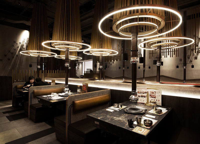 The designers of this restaurant in Hong Kong, utilized raw materials to generate a modern and futuristic atmosphere, with wood covered range hoods above each table highlighted by circular lighting. #ModernRestaurant #RestaurantDesign