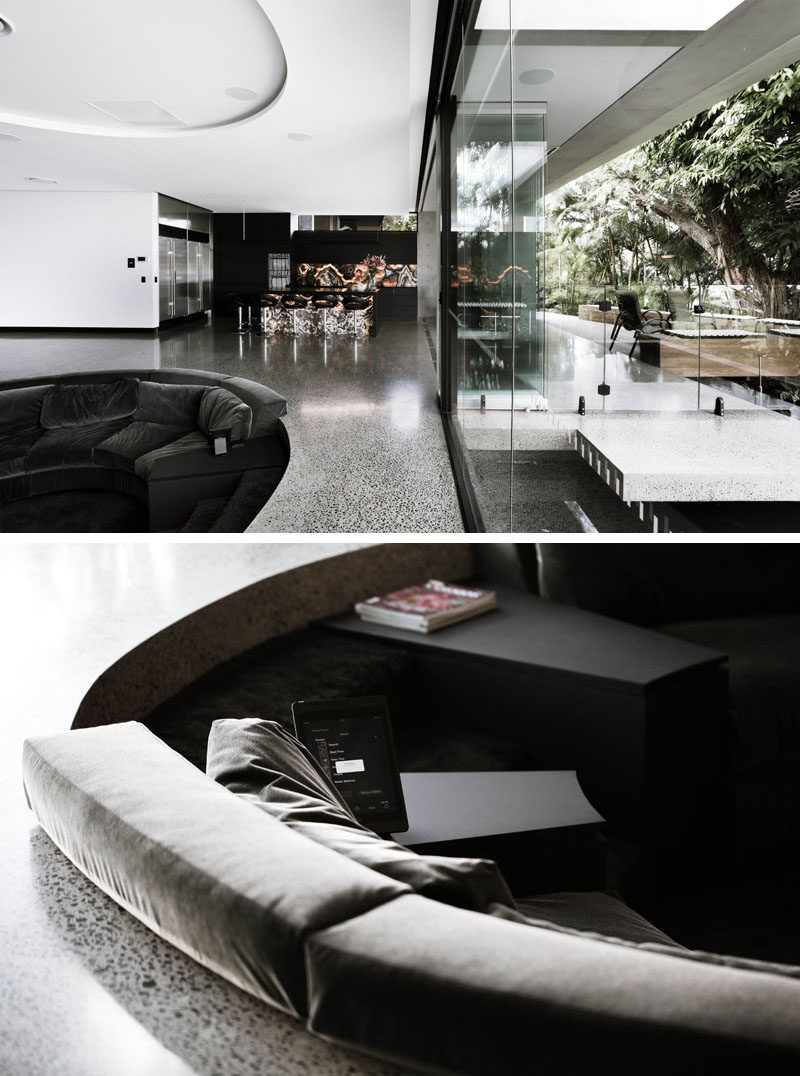 This sunken living room has steps that lead down into the seating area, where plush upholstered seating and cushions wrap around the interior. A more form fitting and structured cushion meets the concrete flooring, making sure there aren't any hard edges seen or felt. #SunkenSeating #SunkenLivingRoom