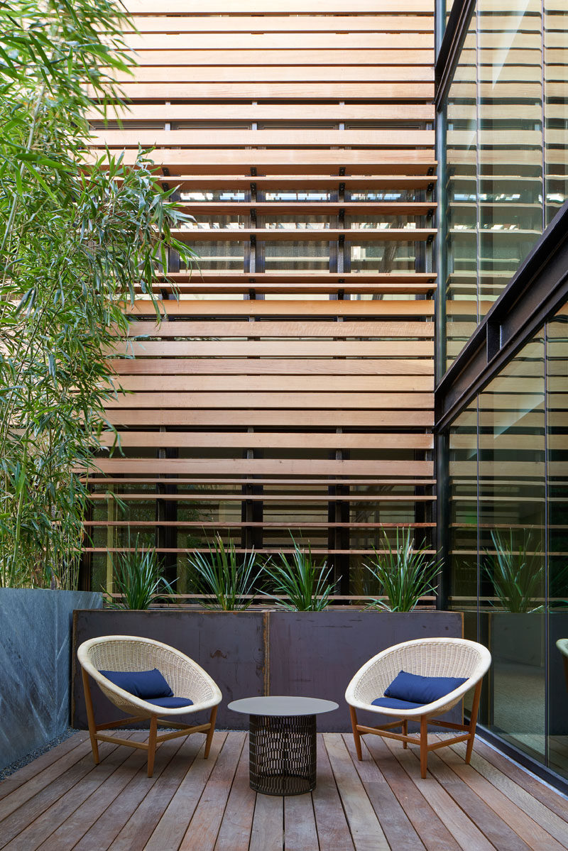This modern hotel has a small seating area for two that's surrounded by glass, wood, and plants. #HotelDesign #OutdoorSpace