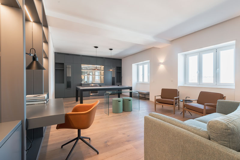 This modern apartment has a large office with a built-in desk, and a pool table that's positioned alongside a custom built-in bar. #HomeOffice #GamesRoom
