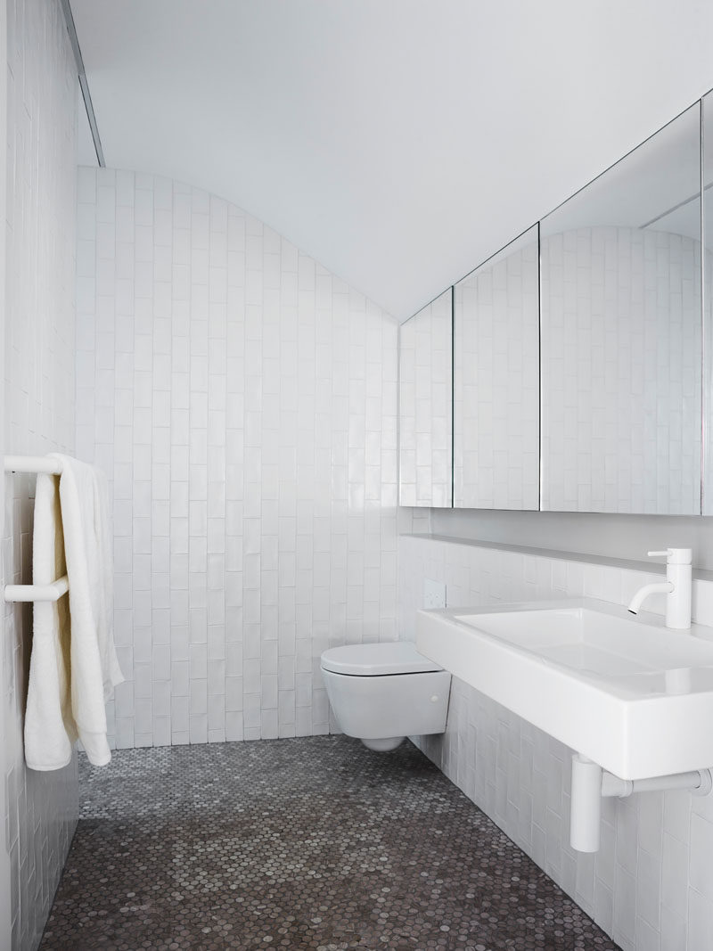 In this bathroom, penny tiles cover the floor while white subway tiles, laid vertically, cover the walls, and the mirrors reflect the light and curve in the ceiling. #ModernBathroom #BathroomDesign