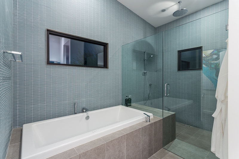 In this modern bathroom, a glass shower screen separates the shower from the built-in bath. The glass screen also allows the light from both windows to filter throughout the space. #ModernBathroom #BathroomDesign