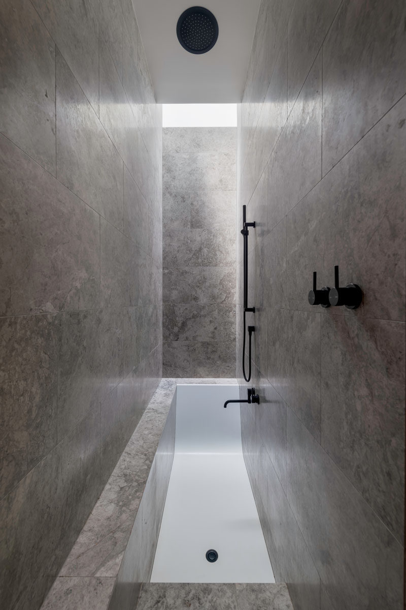 This modern tile-covered ensuite bathroom features a sunken bath with steps that lead down into it. #ModernBathroom #SunkenBath
