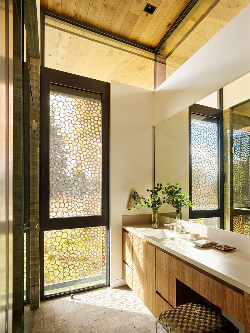 In this modern bathroom, a pierced steel curtain provides privacy without compromising the natural light. #Bathroom #PrivacyScreen