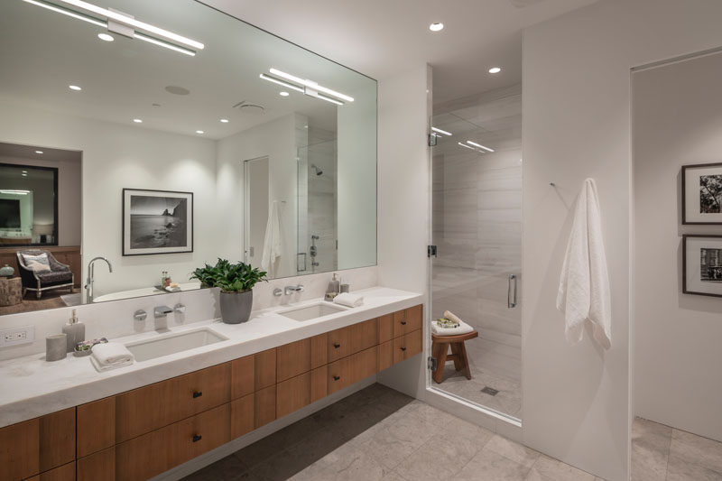 In this modern master bathroom, the Sinker Cypress has been used for the dual-sink vanity, while a glass door separates the shower from the rest of the room, and a freestanding bathtub is located opposite the vanity. #MasterBathroom #BathroomDesign #ModernBathroom