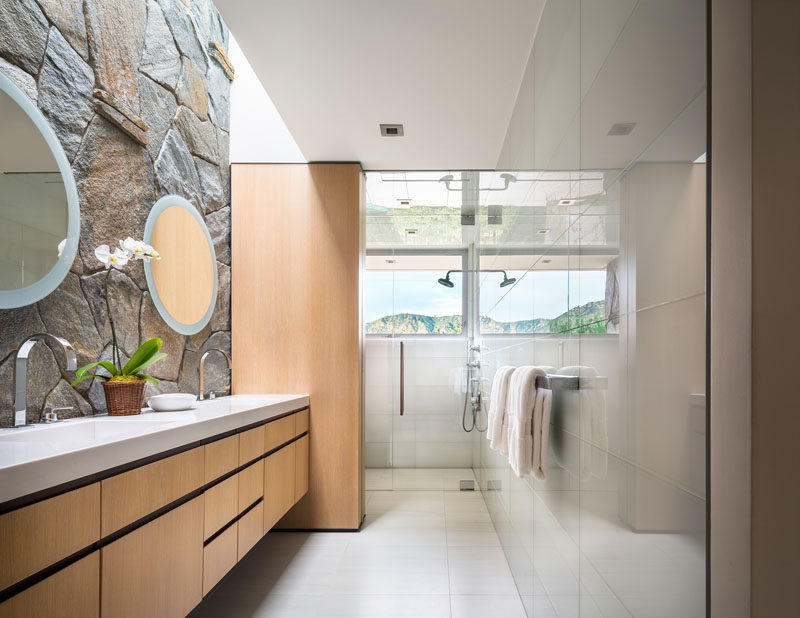 In this modern bathroom, a stone wall becomes the backdrop for the vanity, while a horizontal window in the shower allows natural light into the room. #StoneWall #ModernBathroom