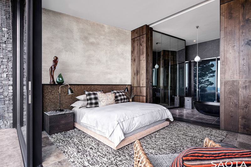 This modern bedroom features an ensuite bathroom that's open to the rest of the bedroom, allowing it to take advantage of the views. #BedroomDesign #ModernBedroom