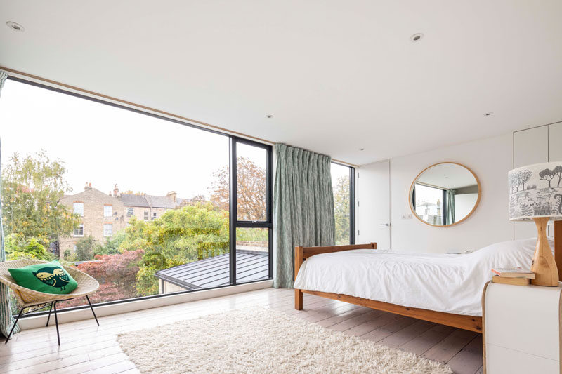 A large picture window fills this modern bedroom with natural light and frames views of the garden. #PictureWindow #ModernBedroom