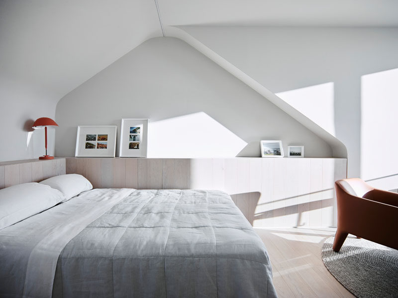 In this modern bedroom, large windows provide natural sunlight to filter through, while a cabinet lines the wall beneath a curved alcove. #ModernBedroom #BedroomDesign