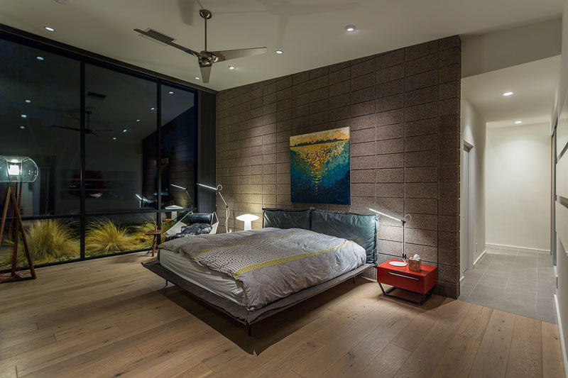 This modern master bedroom opens to the exterior, while the blockwork creates an accent wall for the master bed and flows from inside to out. #ModernMasterBedroom #Windows #BedroomDesign